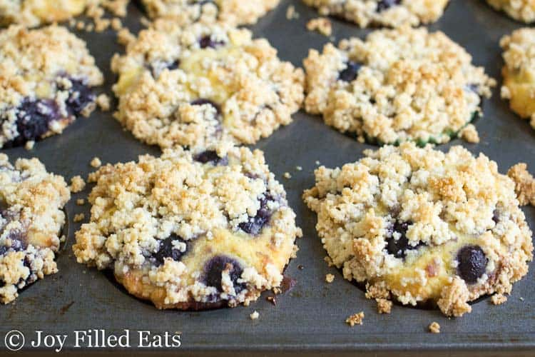 muffin tin full of blueberry muffins with crumb topping