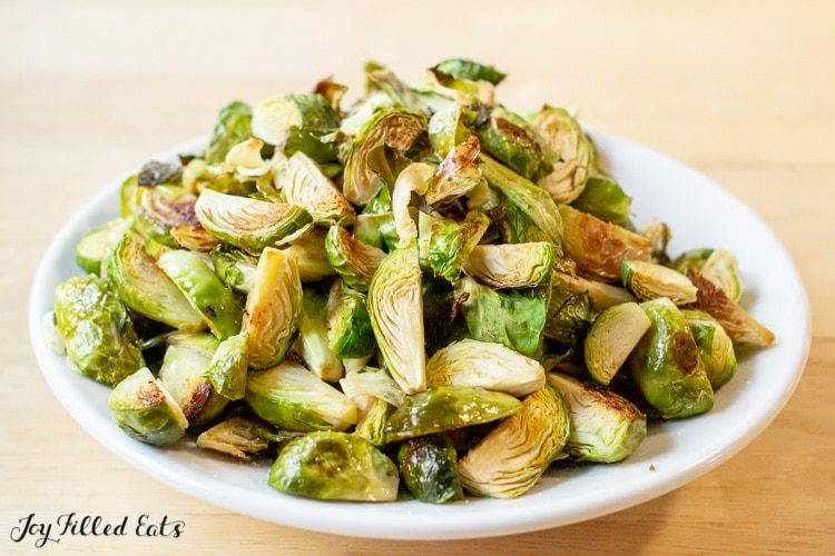 pile of roasted Brussels sprouts in a shallow white dish