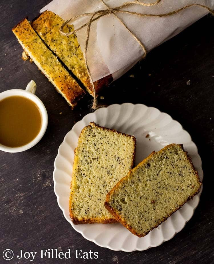 Slices of Lemon Poppy Seed Loaf Cake on a white plate with the parchment wrapped loaf on the side