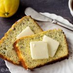 two slices of lemon poppy seed loaf cake topped with pads of butter on a white plate