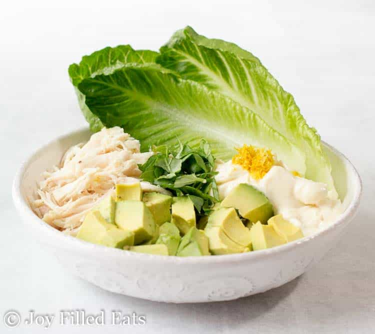 bowl full of ingredients for chicken salad with avocado wrapped in lettuce