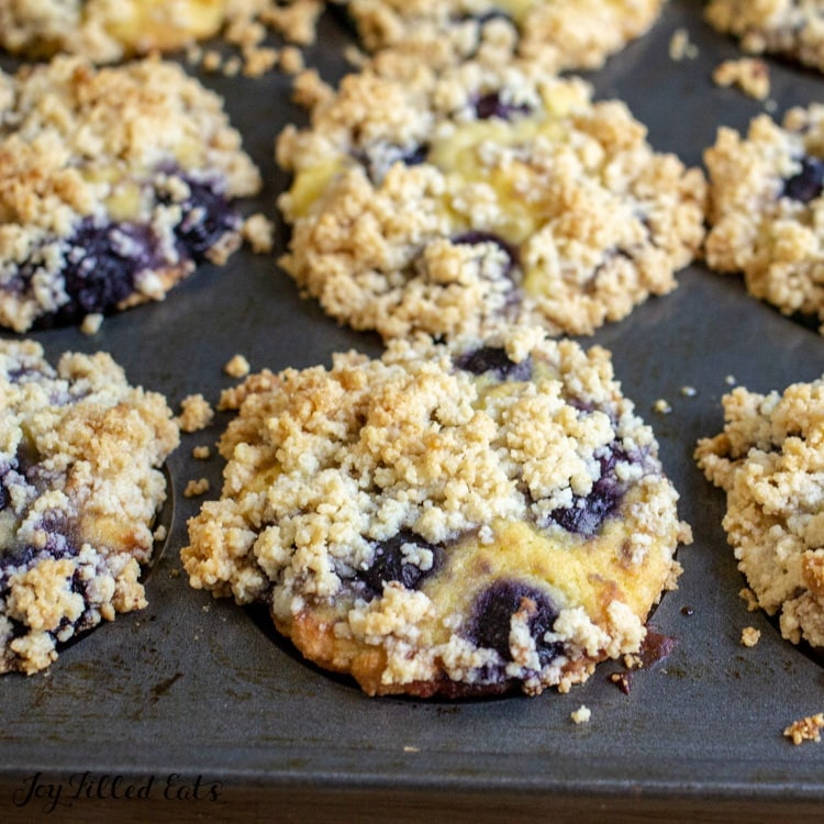 muffin tin full of low carb blueberry muffins with crumb topping