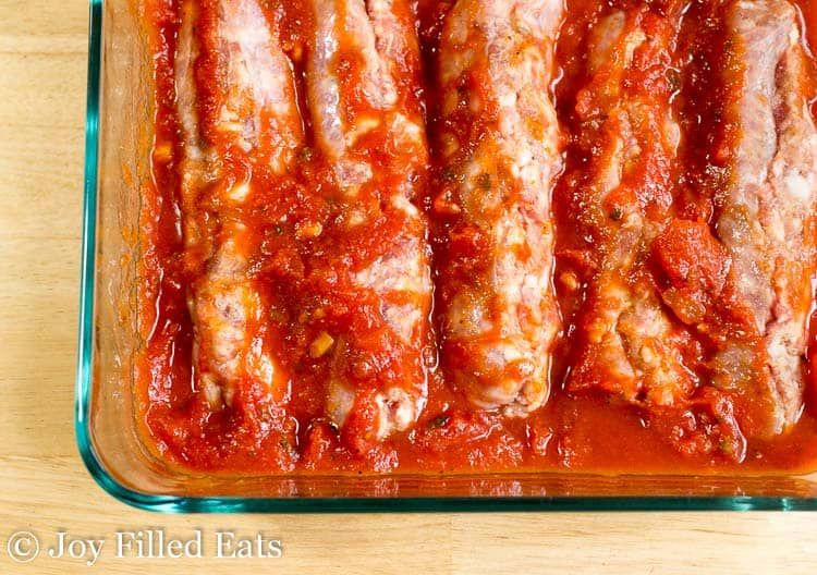 close up on casserole dish lined with sausage covered in marinara sauce