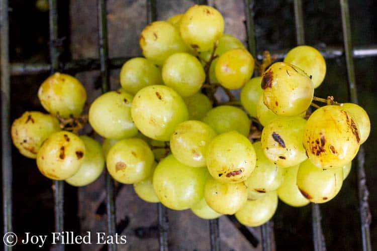 bunch of grilled green grapes on a grill from above