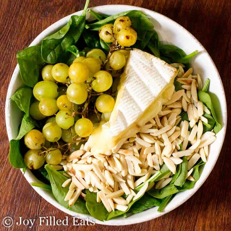 bowl of spinach salad topped with grilled grapes, brie cheese and pine nuts