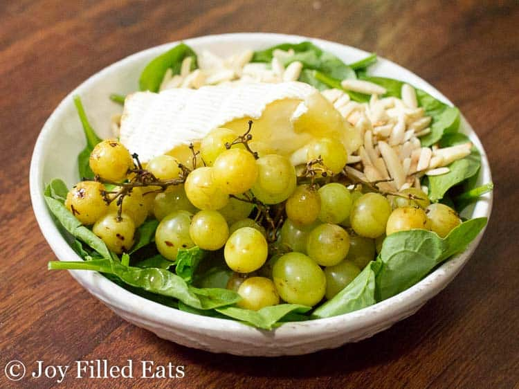 bowl of spinach salad with grilled grapes and brie cheese
