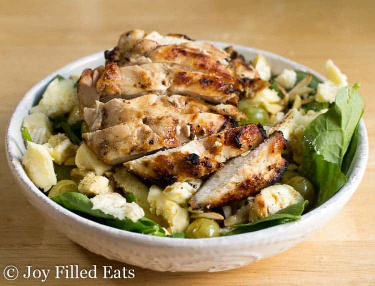 lemon grilled chicken sliced on top of a spinach salad in a white bowl