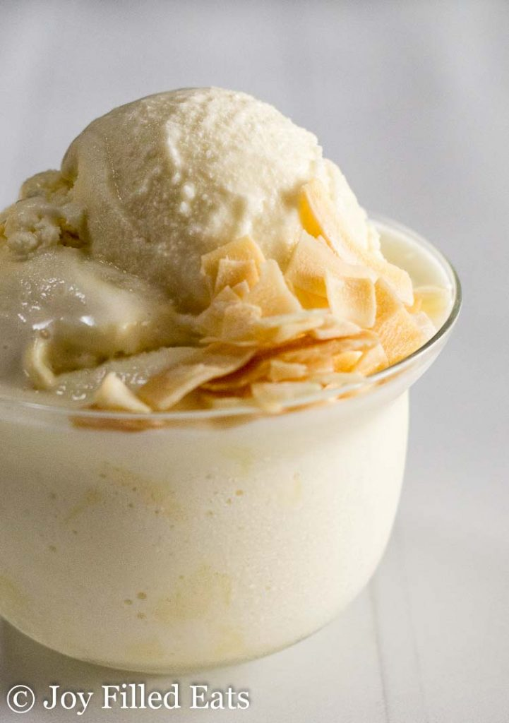 scoop of pina colada ice cream topped with coconut flakes in a small glass bowl