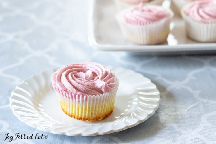 one raspberry frosted cupcake placed on a white circular plate next to a platter of more cupcakes