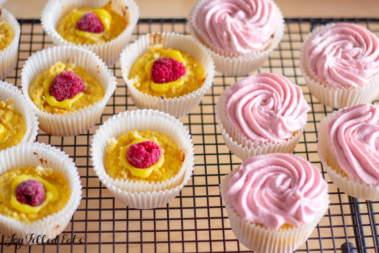 keto lemon cupcakes arranged on a cooling rack, half topped with a center lemon filling with fresh raspberry and half topped with raspberry frosting