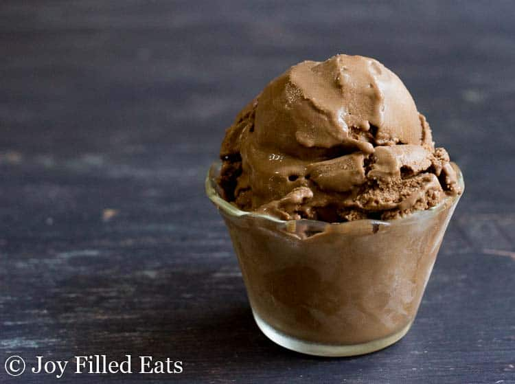 two scoops of chocolate dairy free ice cream in a small glass bowl