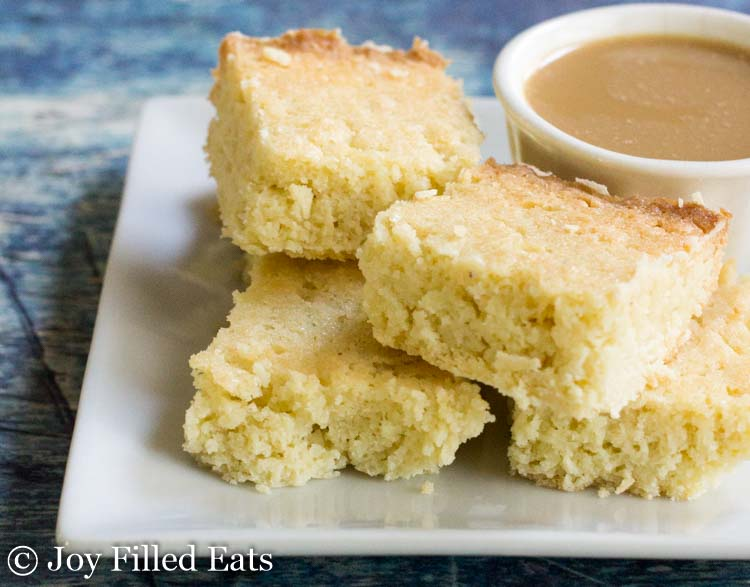 close up on stack of white chocolate blondies next to a cup of coffee