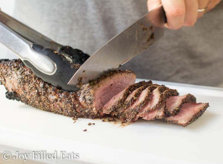 hand using chef's knife and tongs to slice girlled london broil