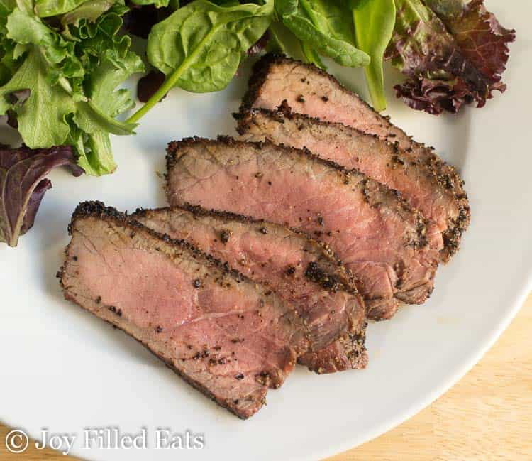 slices of grilled london broil on a plate with a mixed green salad