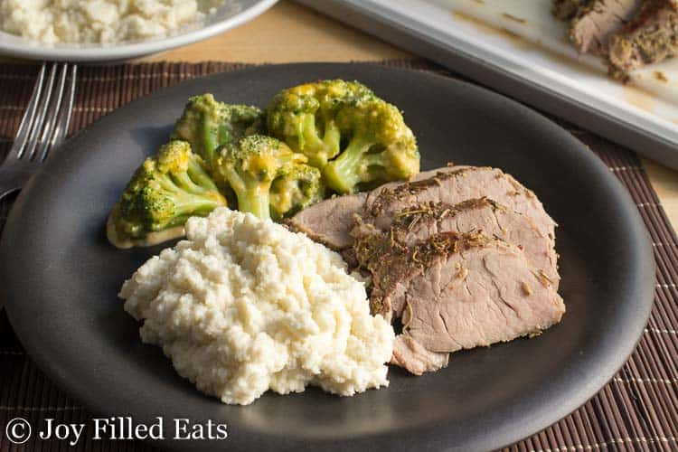 blake plate of sliced pork tenderloin, broccoli and mashed cauilflower