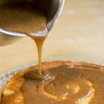 Caramel Frosting being poured onto banana cake close up
