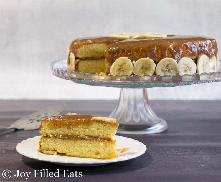 Easy Banana Cake Recipe with Caramel Frosting aka Bananas Foster Cake on a cake stand and a slice on a white plate