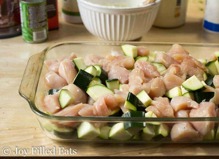 raw chicken and cubed zucchini in a glass baking dish