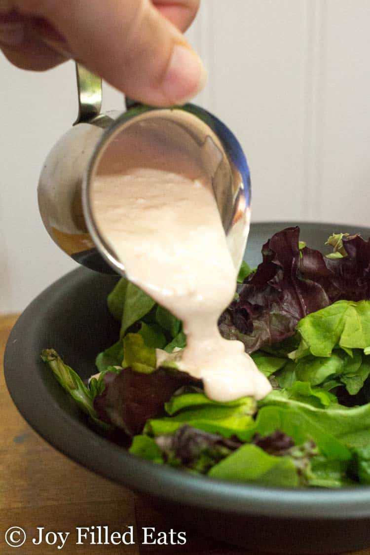 hand holding small pitcher pouring creamy garlic salad dressing onto mixed greens