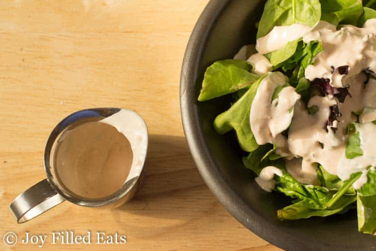 bowl of mixed greens topped with creamy garlic salad dressing next to a small pitcher filled with more salad dressing