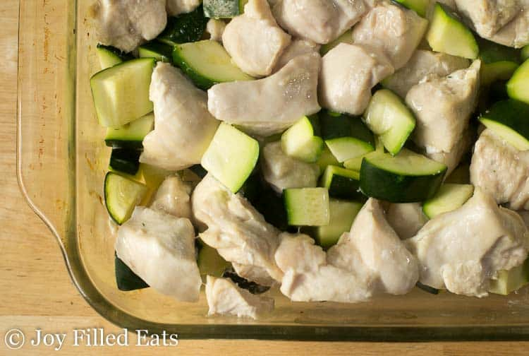 cooked chicken and zucchini in a glass baking dish