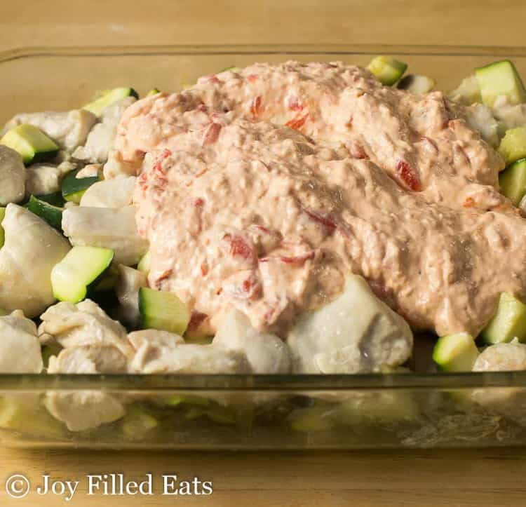 creamy sauce poured over cubed chicken and zucchini in casserole dish