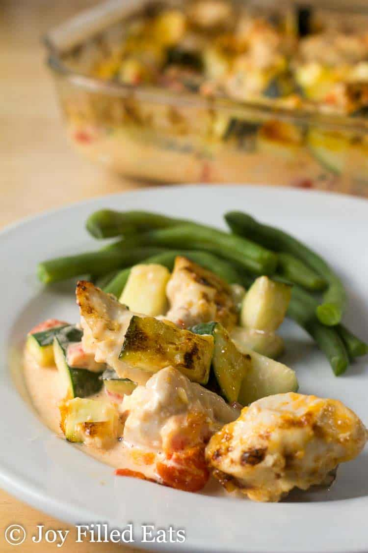 chicken zucchini casserole serving with a side of green beans on a white plate