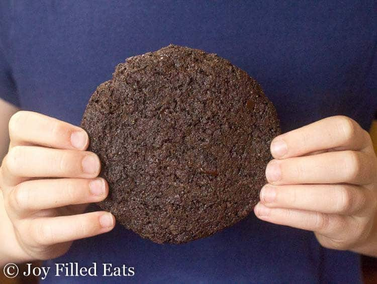 hands holding a large triple chocolate cookie against a blue shirt