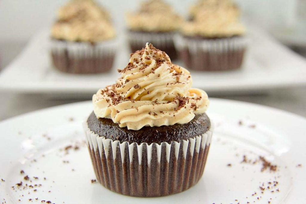 close up on chocolate cupcake on a white plate topped with peanut butter frosting