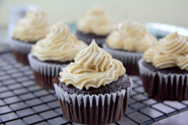 chocolate cupcakes with peanut butter frosting lined on a cooling rack close up
