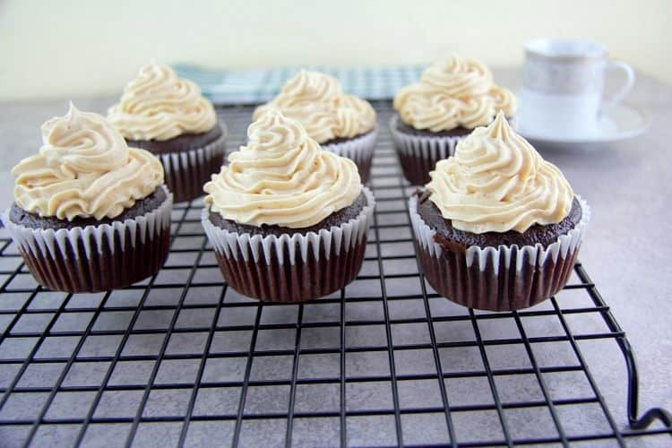 chocolate cupcakes with peanut butter frosting lined on a cooling rack