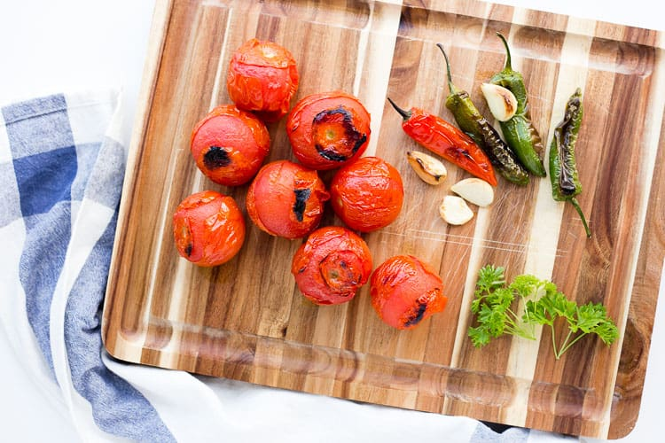 roasted tomatoes, roasted peppers, roasted garlic and herb placed on a cutting board