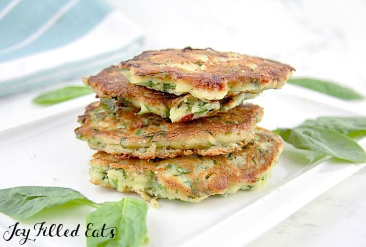 stack of spinach & feta pancakes on a white platter surrounded by spinach leaves