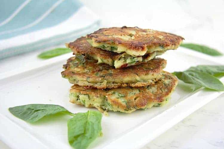 stack of spinach & feta savory pancakes on a white platter surrounded by spinach leaves
