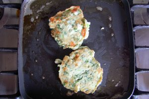 griddle with two spinach & feta pancakes cooking