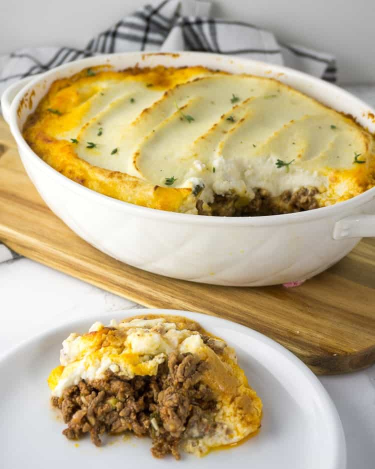 white plate of keto Shepherd's pie serving next to large casserole dish on a wooden cutting board of remaining Shepherd's pie