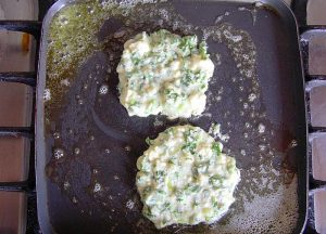 griddle with batter for two spinach & feta pancakes cooking