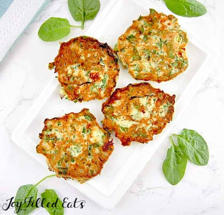 spinach & feta pancakes arranged on a white platter surrounded by spinach leaves
