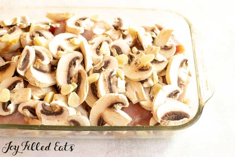 raw chicken thighs in a glass baking dish topped with sliced mushrooms and garlic