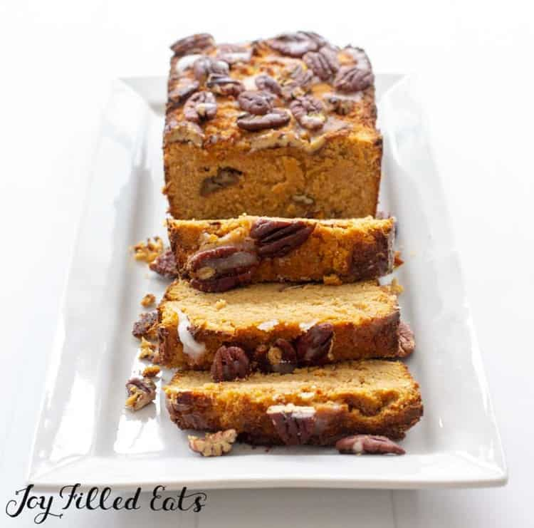 pumpkin bread loaf topped with pecans on a white platter with three slices cut from loaf