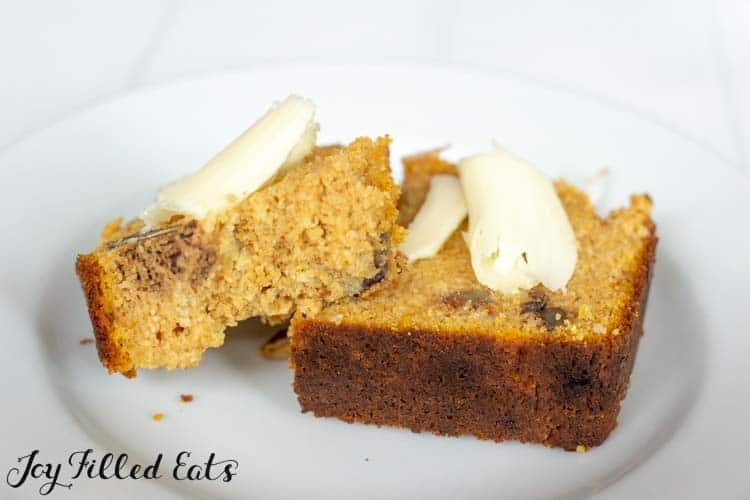 plate with two pieces of pumpkin bread with a shaving of butter on top of each piece