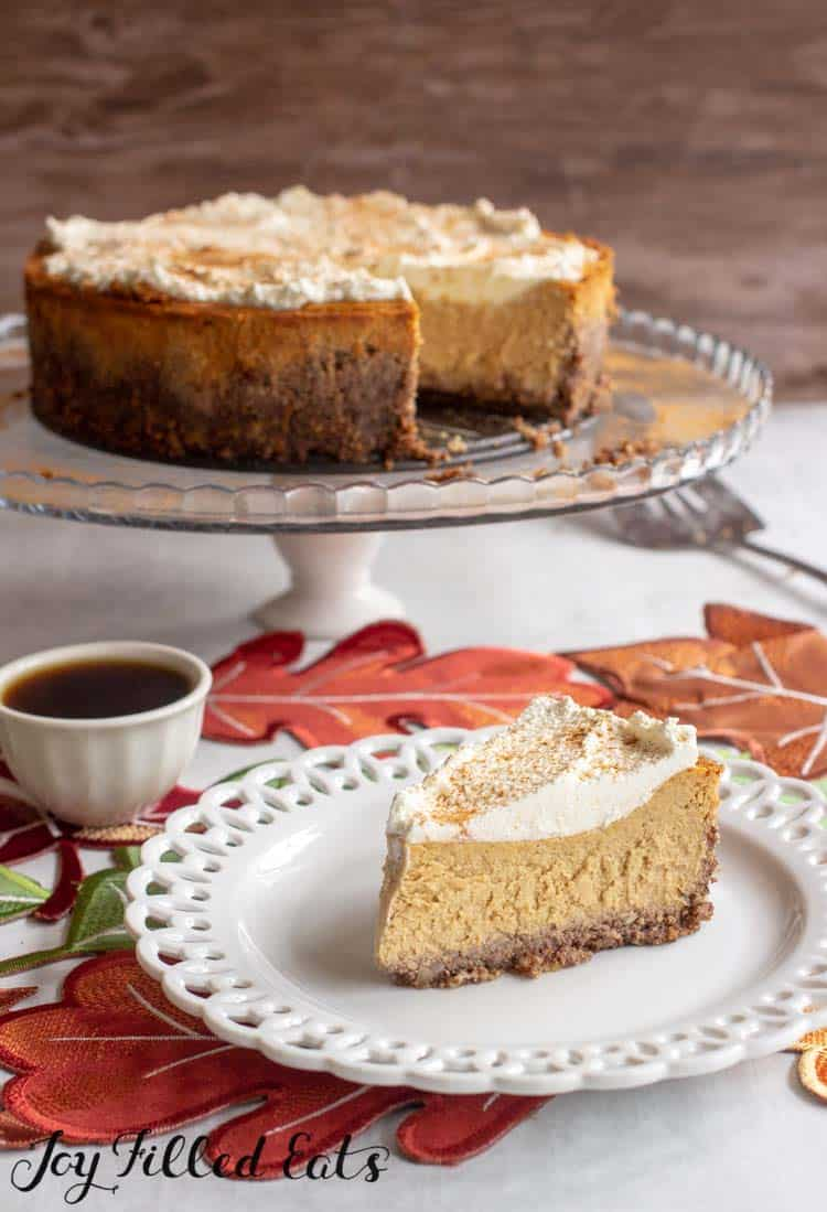 Keto Pumpkin Cheesecake Recipe slice on a white plate with the whole cheesecake on a cake stand
