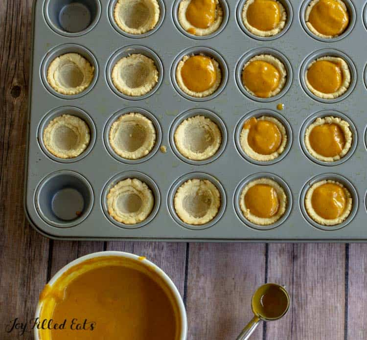 a bowl of mini pumpkin pie filling next to a mini muffin tin filled with both pie crusts and pie crusts with pumpkin filling