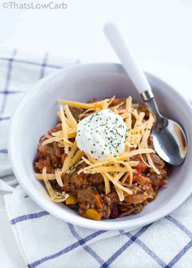 spoon and bowl of slow cooker no bean chili topped with sour cream and shredded cheese