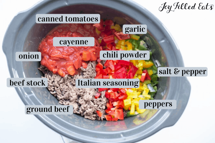 Slow Cooker No Bean Chili ingredients including canned tomatoes, cayenne, garlic, chili powder, onion, beef stock, italian seasoning, ground beef, peppers, salt and pepper
