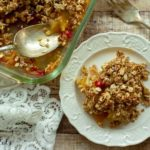casserole dish with serving spoon full of apple crisp next to a plate with a serving of apple crisp