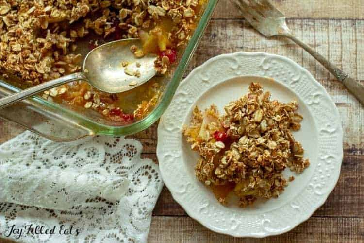Overhead shot of the apple crisp with oats on a white plate with a fork