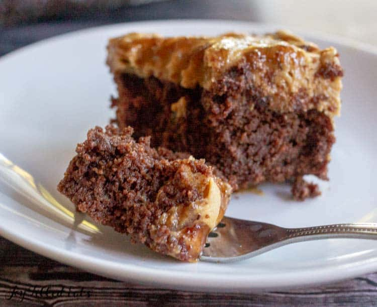 bite of caramel macchiato brownie on a fork resting on a plate with remaining brownie