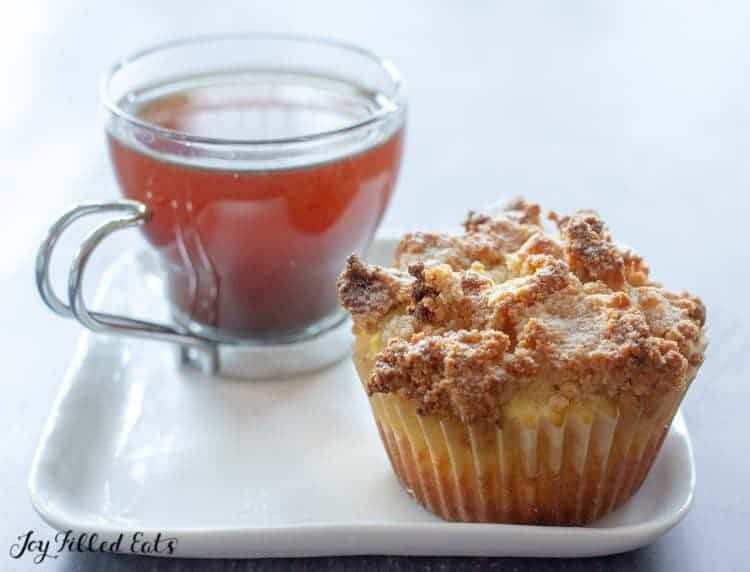 coffee cake muffin next to a glass teacup with tea on a square white plate