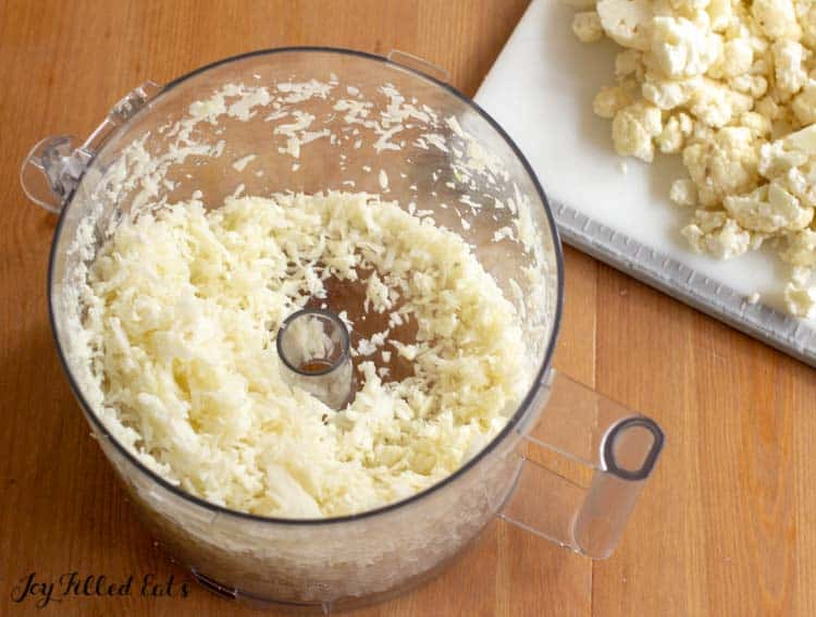 food processor filled with riced cauliflower next to a cutting board of cauliflower florets